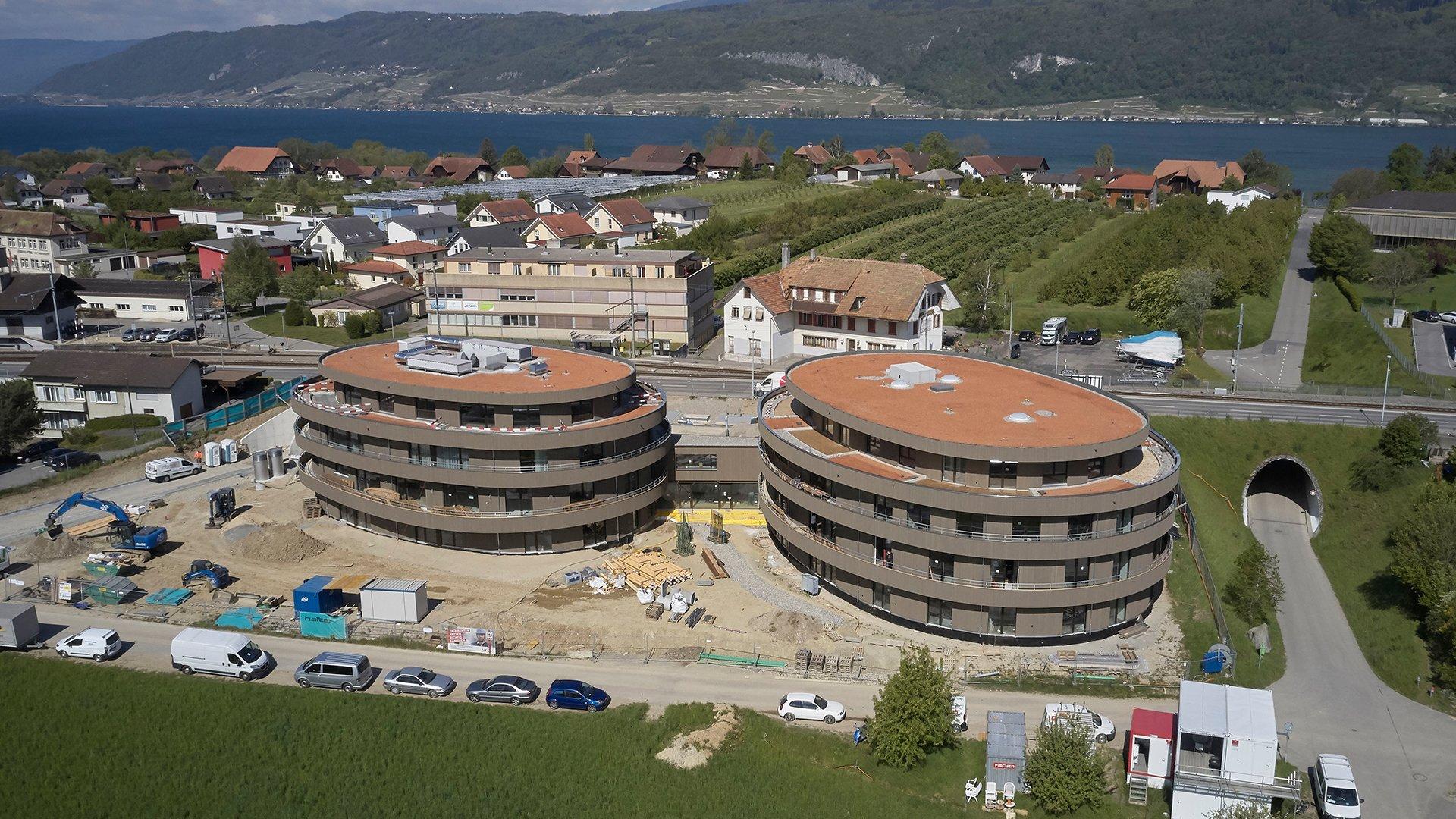 Drohnenaufnahmen Bauphase Gebäude mit See im Hintergrund