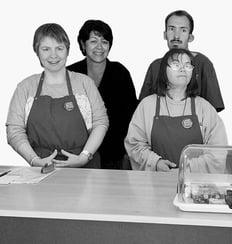 Team LadenBistro Biel: zwei personen im Hintergrund und zwei Personen im Vordergrund mit einer Schürze an einem Tisch stehen